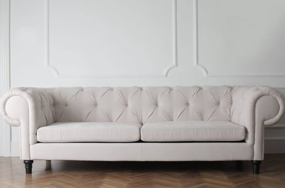 A white couch reassembled by cross-country movers